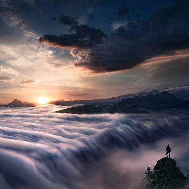 Man on top of Mountain over clouds
